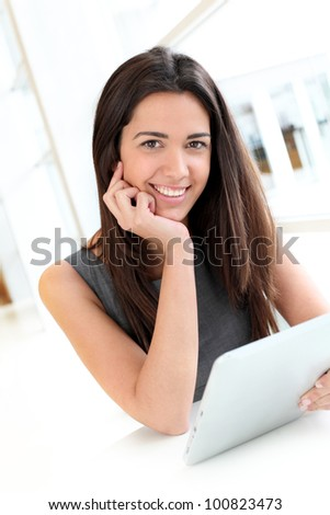 Portrait of smiling student using electronic tablet - stock photo