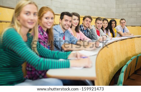 Portrait of smiling students sitting in a row at the college lecture hall - stock photo