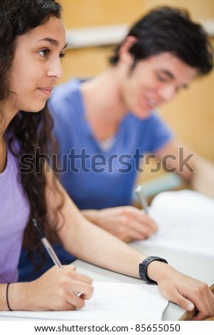 Portrait of smiling students writing in an amphitheater - stock photo