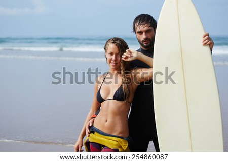 Portrait of smiling surfer couple standing on the beach against amazing ocean view, fashionable handsome man embracing his girlfriend and holding surf board with copy space area for advertising text - stock photo