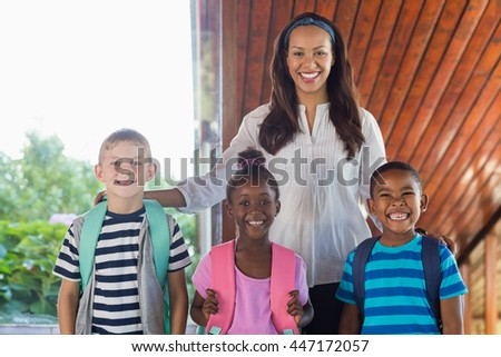 Portrait of smiling teacher and kids standing together with arm around at school - stock photo