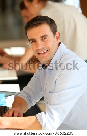Portrait of smiling teacher at school - stock photo