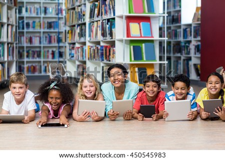Portrait of smiling teacher with students using digital tablets while lying down in library - stock photo
