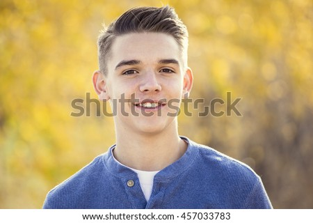 Portrait of smiling teen boy outdoors. Boy looking at the camera with a handsome smile on his face - stock photo