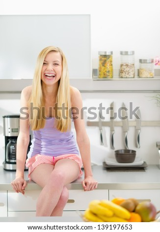 Portrait of smiling teenager girl sitting in modern kitchen - stock photo