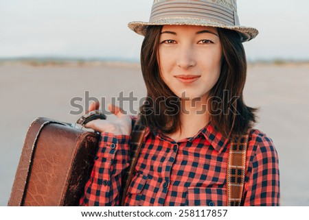 Portrait of smiling traveler young woman with suitcase - stock photo