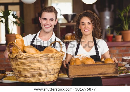 Portrait of smiling waiter and waitress holding basket full of bread rolls at coffee shop - stock photo