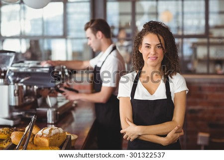 Portrait of smiling waitress with arms crossed in front of colleague at coffee shop - stock photo