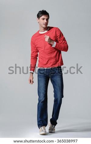 portrait of smiling walking man casuals in studio - stock photo