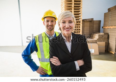 Portrait of smiling warehouse worker and his manager in a large warehouse - stock photo
