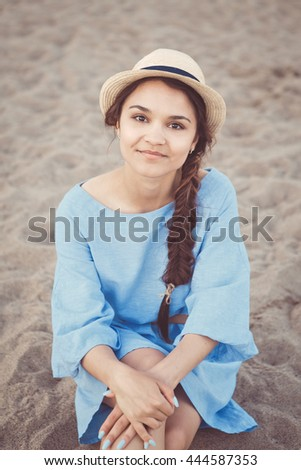 Portrait of smiling white Caucasian brunette woman with tanned skin in blue dress and straw hat sitting on sand beach shore, sunset on summer day, lifestyle concept - stock photo