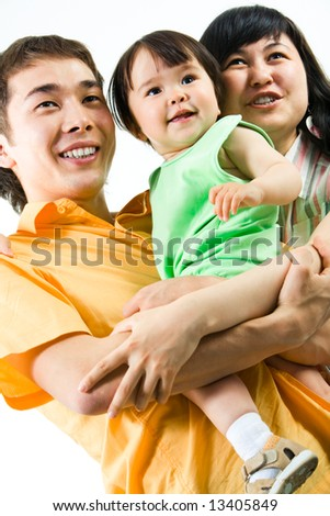 Portrait of smiling woman and man holding little daughter - stock photo