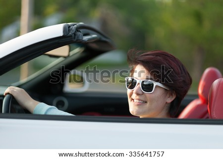 Portrait of smiling woman driving a convertible sports car with red leather interior. Shallow depth of field. - stock photo