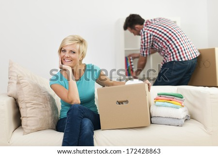 Portrait of smiling woman during the decorating new living room - stock photo
