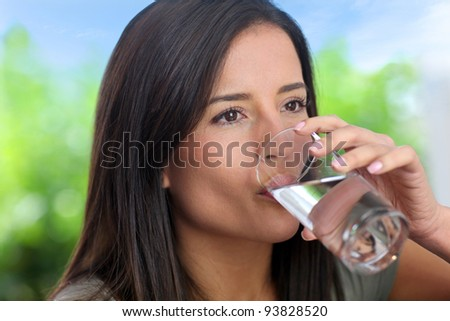 Portrait of smiling woman holding glass of water - stock photo