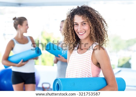 Portrait of smiling woman holding yoga mat in fitness studio - stock photo