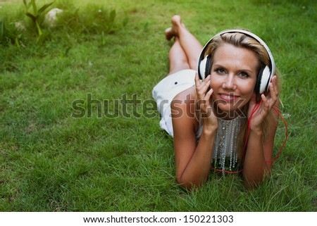 portrait of smiling woman in headphones lying on the grass - stock photo