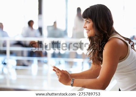 Portrait of smiling woman in office with smart phone - stock photo