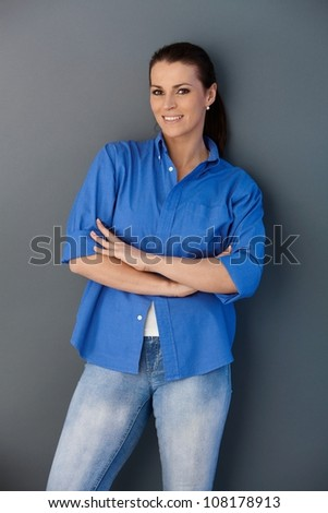 Portrait of smiling woman standing at wall with arms crossed, looking at camera. - stock photo