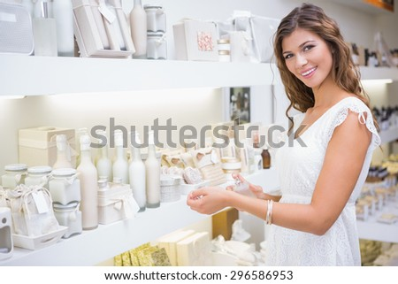 Portrait of smiling woman testing perfume at a beauty salon - stock photo