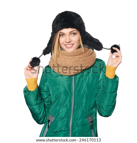 Portrait of smiling woman wearing green winter jacket and warm fur hat, over white background - stock photo