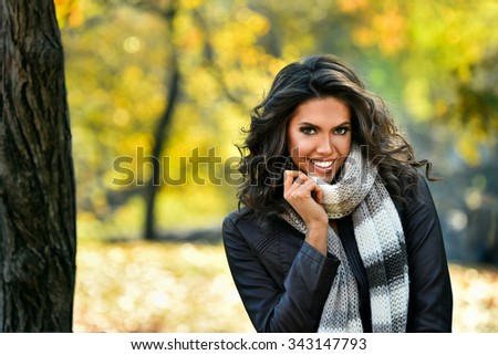 Portrait of smiling woman wearing leather jacket and scarf. Young woman in beautiful autumn park, concept autumn. - stock photo