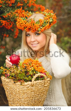 Portrait of smiling woman wearing woolen accessories. woman in orange wreath with red apple in hand. Portrait of beautiful young woman walking outdoors in autumn - stock photo
