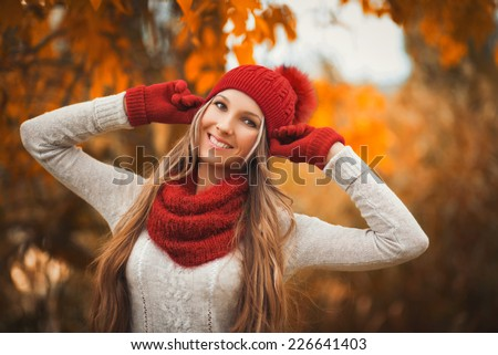 Portrait of smiling woman wearing woolen accessories. Young woman in beautiful autumn park, concept autumn - stock photo