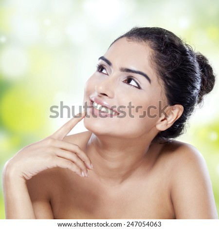 Portrait of smiling woman with beautiful face and smooth skin looking at copyspace against bokeh background - stock photo