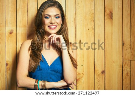 Portrait of smiling woman with long hair against wooden background. Beautiful female model. - stock photo