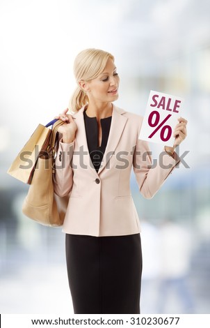 Portrait of smiling woman with many shopping bags standing in shop and holding hand percentage sign.  - stock photo