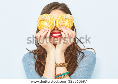 Portrait of smiling woman with two cakes in their eyes. Female young model. - stock photo