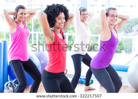 Portrait of smiling women exercising with hands behind head in fitness studio - stock photo
