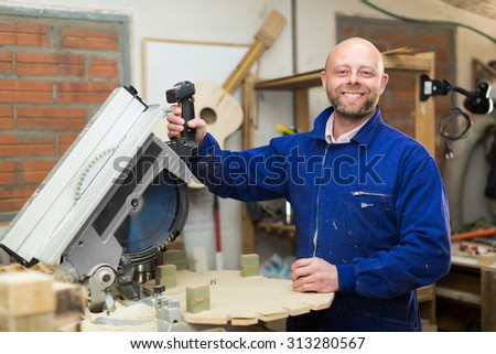 Portrait of smiling woodworker working on a machine at wood workshop - stock photo