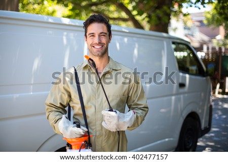Portrait of smiling worker with pesticide sprayer while standing by van - stock photo