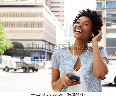 Portrait of smiling young african american woman listening to music on headphones outdoors on city street - stock photo