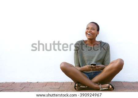 Portrait of smiling young african woman sitting on floor with mobile phone  - stock photo