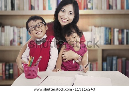 Portrait of smiling young asian mother with her children. shot in the library - stock photo
