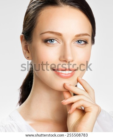 Portrait of smiling young attractive businesswoman, on grey - stock photo