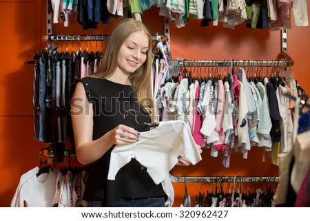 Portrait of smiling young beautiful woman shopping, standing in department store with baby clothes, choosing new outfit for child, holding hanger with cute white blouse, looking at fabric quality - stock photo