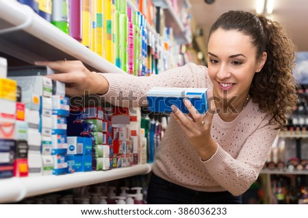 Portrait of smiling young brunette selecting dental treatment in drugstore - stock photo