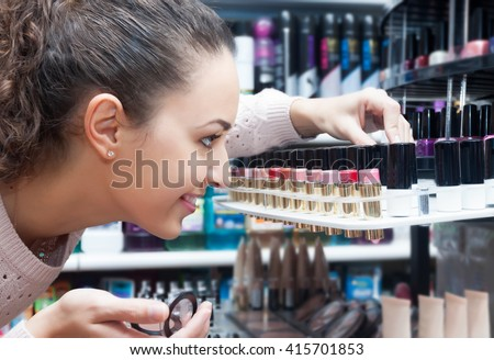 Portrait of smiling young brunette selecting lipstick in a cosmetics shop - stock photo