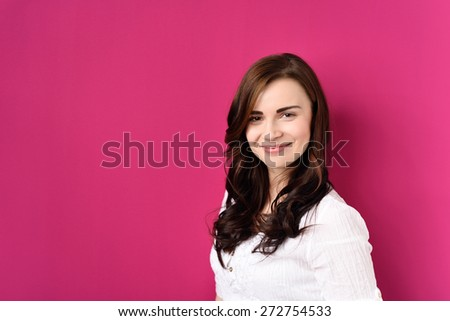Portrait of Smiling Young Brunette Woman Wearing White Top and Leaning Against Bright Pink Wall - stock photo