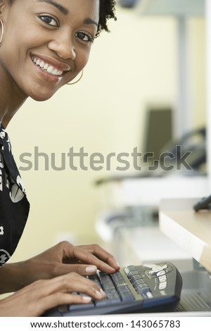 Portrait of smiling young businesswoman typing on computer keyboard in office - stock photo