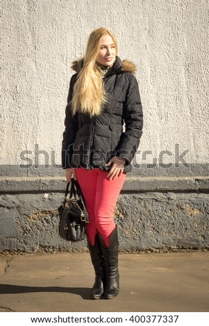 Portrait of smiling young caucasian woman with long blond hair wearing parka and boots carrying a bag standing against a gray wall - stock photo
