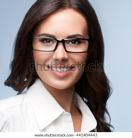 Portrait of smiling young cheerful brunette businesswoman in glasses, over grey background - stock photo