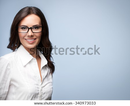Portrait of smiling young cheerful brunette businesswoman in glasses, over grey background, with copyspace - stock photo