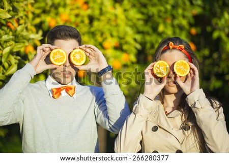 Portrait of smiling young couple holding oranges over eyes. - stock photo