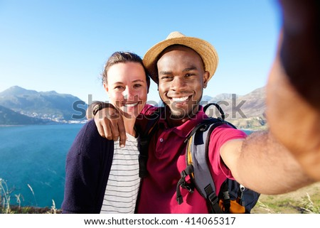 Portrait of smiling young couple on vacation taking selfie with mobile phone - stock photo