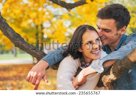 Portrait of smiling young couple outdoors in autumn having fun time - stock photo